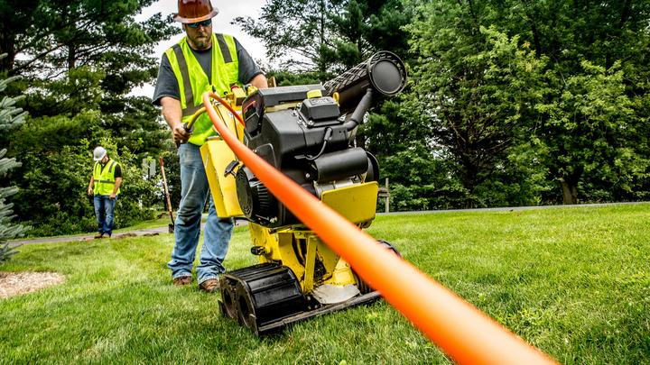 Image of a man using equipment to lay fiber cable into ground